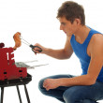 jonge man grillen kip — Stockfoto