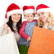 Two women and little girl in Santa hat - Stock Photo