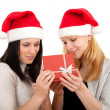 Two women in Santa hat with red box - Stock Photo