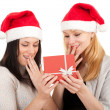 Two women in Santa hat with red box — Stockfoto