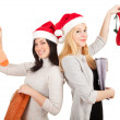 Two women in Santa hats with bags - Stock Photo
