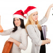 Two women in Santa hats with bags — Stock Photo