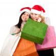 Two women in Santa hats with bags — Stok fotoğraf