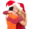 Hugging two women in Santa hats — Stockfoto