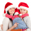 Two women and little girl in Santa hat — Stock Photo