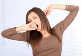 Yawning and stretching beautiful woman — Stock Photo