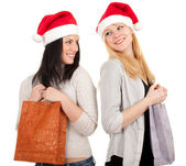 Women in Santa hats with present bag — Stock Photo