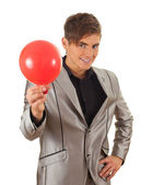 Young man inflating green balloon — Stock Photo