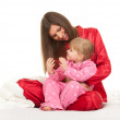Little girl with mother in bedding — Stock Photo