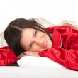 Woman in red pajamas in bedding — Stock Photo #4549709