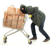 Thief in balaclava with shopping cart — Stock Photo