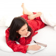 Writting on clipboard woman in pajamas - Lizenzfreies Foto