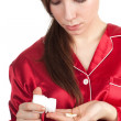 Woman pouring out tablets on palm — Stock Photo