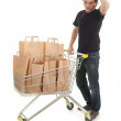 Royalty-Free Stock Photo: Man with paper bags in shopping cart