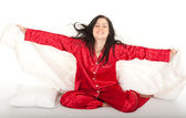 Woman in red pajamas in bedding — Stock Photo