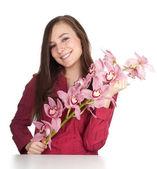Donna giovane sorridente con orchidea — Foto Stock