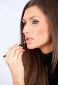 Ung kvinna sätter på lip liner — Stockfoto
