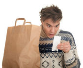 Surprised man with store receipt — Stock Photo