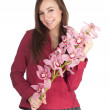 Smiling young woman with orchid — Stock Photo