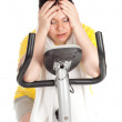 Overweight woman on fitness bicycle — Stock Photo #4954229