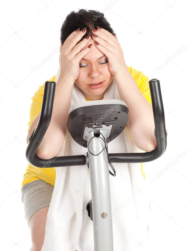 Tired overweight, fat woman in yellow shirt on stationary fitness bicycle