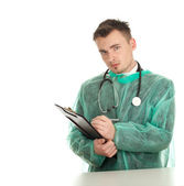 Male doctor writing on clipboard — Stock Photo