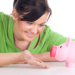 Stock Photo: Girl with pink piggy bank