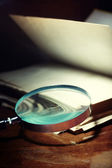 Old book and magnifier — Stock Photo