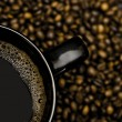Black mug of coffee and scattered beans — Stock Photo