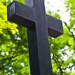 Black wooden cross on green plants background — Stock Photo