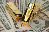 Three gold bars on dollar bills — Stock Photo