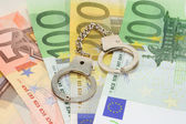 Handcuffs on euro notes — Stock Photo