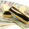Stock Photo: Gold bullion on dollar bills