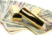 Gold bullion on dollar bills — Stock Photo