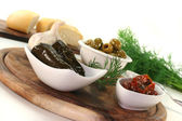 Olives, stuffed vine leaves and dried tomatoes — Stock Photo