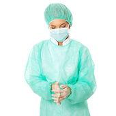 Female surgeon washing her hands — Stock Photo