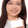 Beautiful businesswoman with business card — Stock Photo #4864381