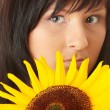 Young woman with a big sun flower - Stock Photo