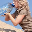 Stock Photo: Thirsty blond woman on desert