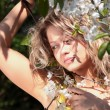 Beautiful blond woman between tree with white flowers - Foto Stock