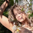 Beautiful blond woman between tree with white flowers - Photo