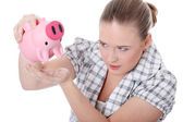 Young woman trying to get money from her piggy — Stock Photo