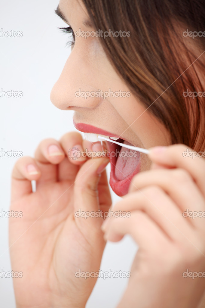 Beautiful young woman using dental floss at bathroom  Stock Photo #4966090