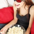 Stock Photo: Beautiful young womwatching TV in 3d glasses