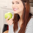 Woman in kitchen eating green apple — Stock Photo