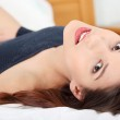 Young and beautiful brunette woman on bed — Stock Photo