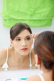 Young woman plucking her eyebrows — Stock Photo