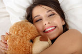 Girl in bed with teddy bear — Stock Photo