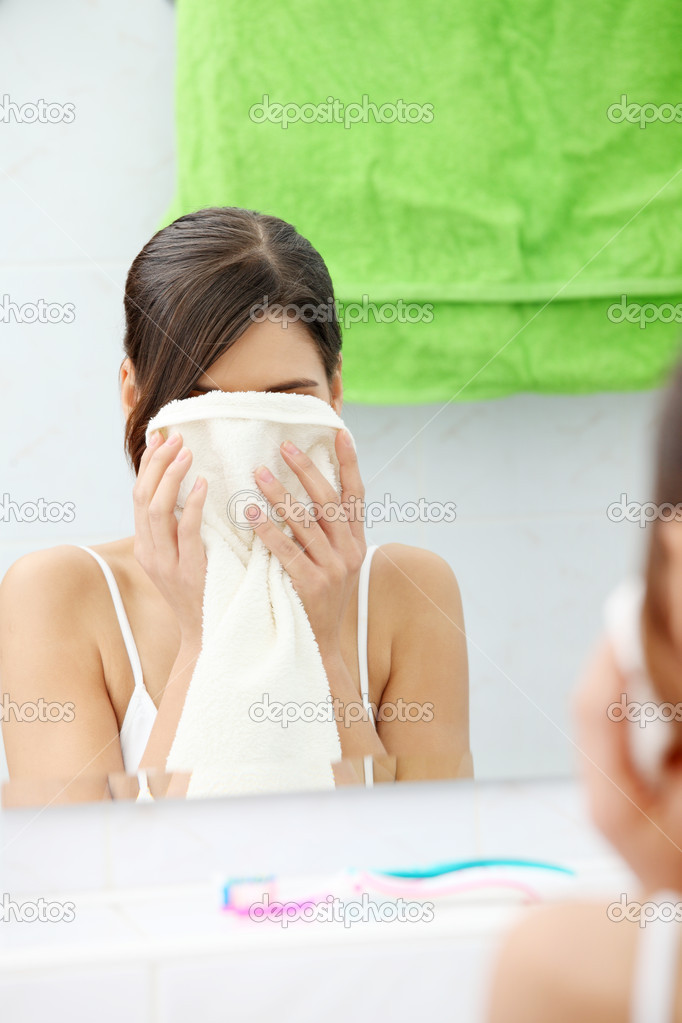 Beautiful woman wipes her face with a towel at bathroom  — Stock Photo #4974774