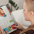 Young woman reading a magazine — Stockfoto